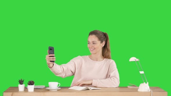 Thumbnail for Beautiful woman taking a selfie with her cell phone sitting