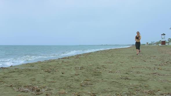Junge Frau mit Fit Body Jogging am Sandstrand am Morgen. Gesundheitswesen