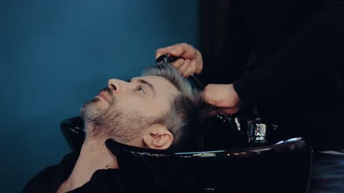 Grayhaired Man Put His Head on the Sink Washes His Hair Before Cutting