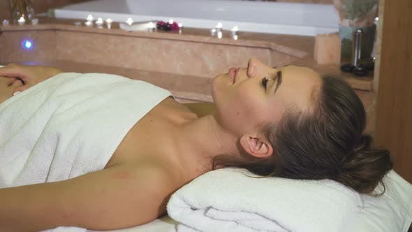 Cover Image for A Girl Enjoying Spa Treatments Looks Into the Camera and Smiles