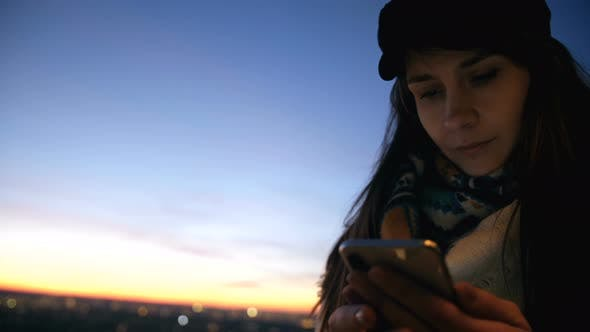 Thumbnail for Low Angle Close-up Young Beautiful Local Woman Using Smartphone App at Incredible Bright Sunset