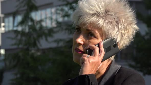 Thumbnail for A Middle-aged Businesswoman Talks on a Smartphone in an Urban Area - Closeup - an Office Building