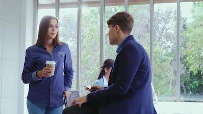 Happy Businesswoman and Businessman Having Conversation in Modern Office