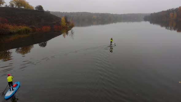 Drone Shot of Man and Woman on Sup Paddle Boards at Wide River on Golden Autumn Forest Background