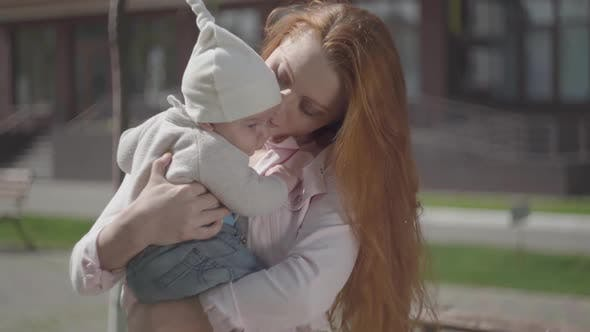 Thumbnail for Portrait Young Pretty Redhead Mother Holding a Cute Baby in Her Arms and Talking To Him in a Spring