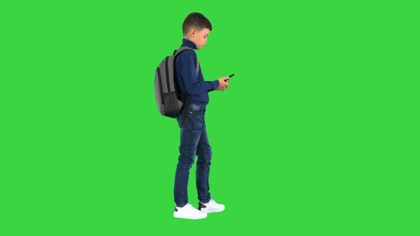 Thumbnail for Schoolboy with a Backpack Using Mobile Phone on a Green Screen Chroma Key