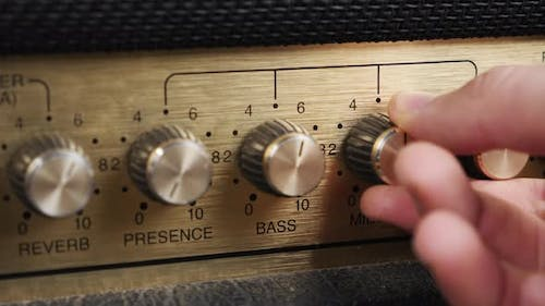 Hand twists tumblers on control panel of guitar amplifier