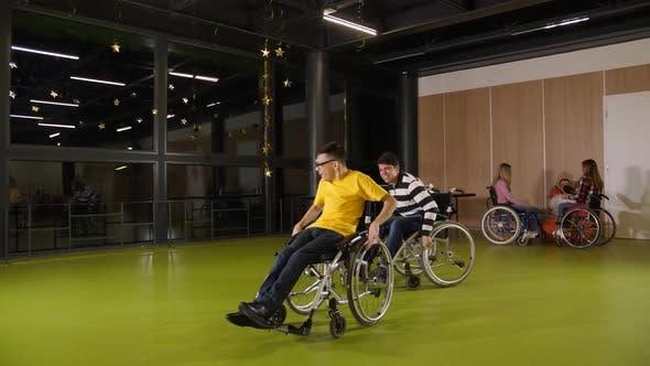 Thumbnail for Joyful Teen Boys Having Fun Racing in Wheelchairs