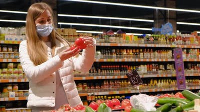 The girl buys tomatoes in the supermarket, natural products