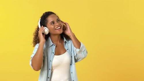 Happy young African American woman in casual wear listening to music on headphones and dancing
