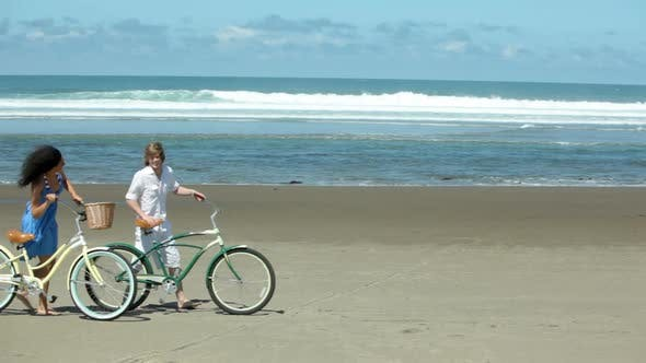 Thumbnail for Couple walk with bicycles along coastline