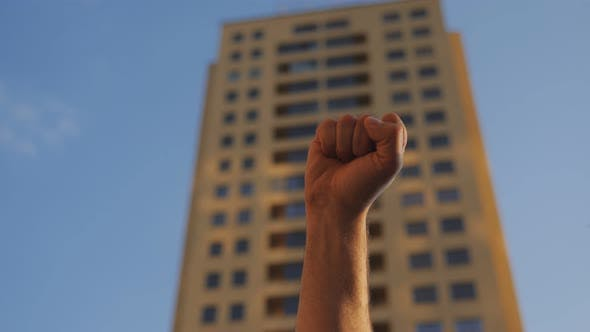 The Man Raises His Hand with a Clenched Fist Up in Protest