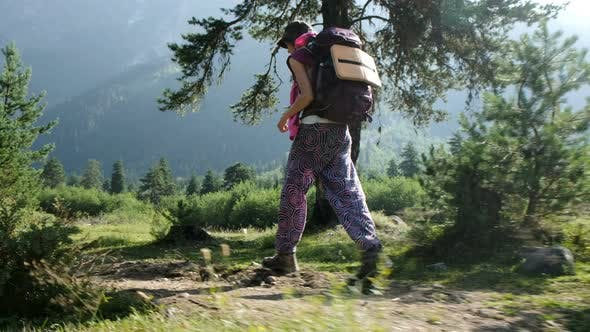 Thumbnail for Young Woman Tourist in Trekking Boots with a Backpack Walking in a Hike Against a Beautiful Mountain
