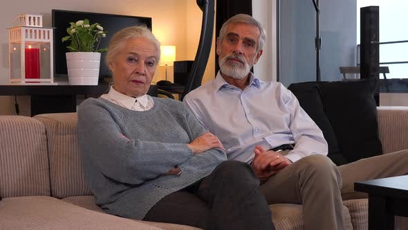 Thumbnail for An Elderly Couple Sits on A Couch in An Apartment and Talks to The Camera