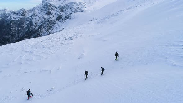 Thumbnail for A Group Of People Going Down The Snowy Peak