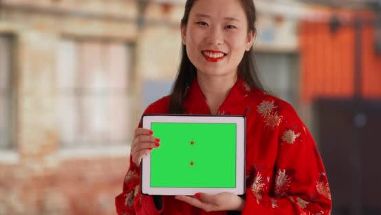 Thumbnail for Close up of attractive woman showing greenscreen on tablet pc in urban setting