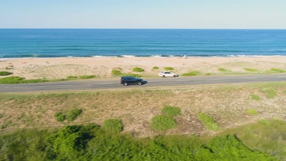 Drone Chasing Fast Driving Black SUV Along Coastal Asphalt Road with Crashing Waves in the