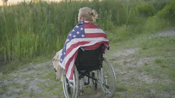 Thumbnail for Back View of Paralyzed Man Wrapped in American Flag Sitting on Wheelchair and Thinking. Wide Shot of