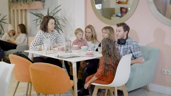 Thumbnail for Happy Adult Women, Man and Little Children Are Sitting at Table in Cozy Cafe