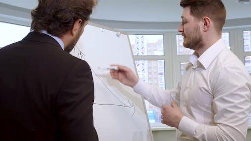 Businessman Draws on the Flip Chart