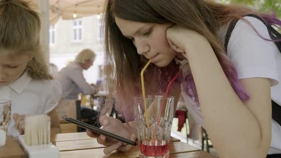 Thumbnail for Teenager Girl with Younger Sister Sitting in an Outdoor Cafe Drinking Juice and Using Smartphone