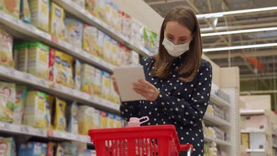 Woman Shopper in Protecting Mask with Cart in the Store Aisle with Grocery List During Shopping Food