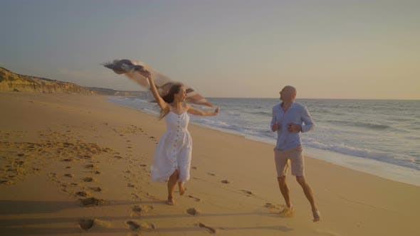 Thumbnail for Happy Couple Running on Beach at Sunset