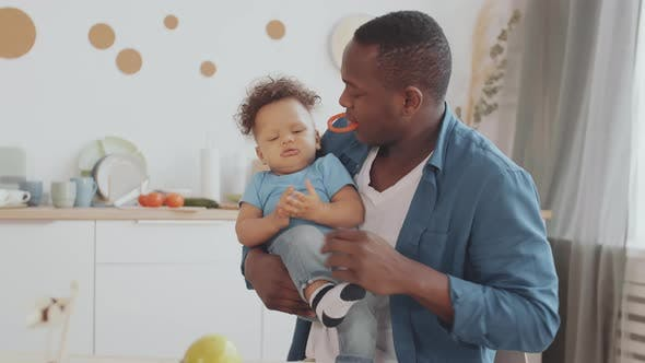 Thumbnail for African Man and Curly-haired Baby Playing