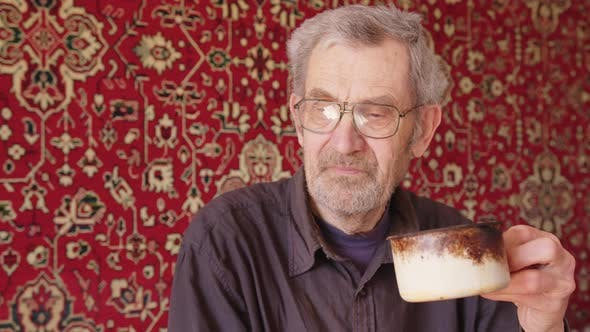Senior Beggar Man Drinking Tea Alone