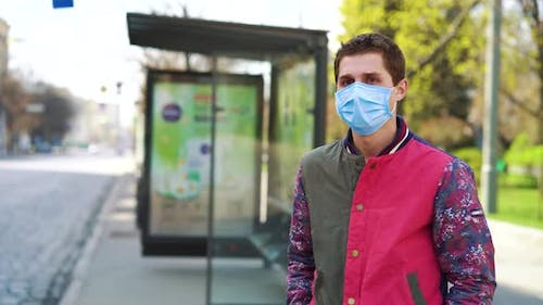 Young Man in Medical Mask Waiting for Bus on Empty Bus Stop