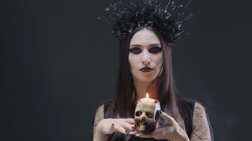 Mystical Female in Black Attire Holds a Skull with a Burning Candle and Looking at the Camera, the