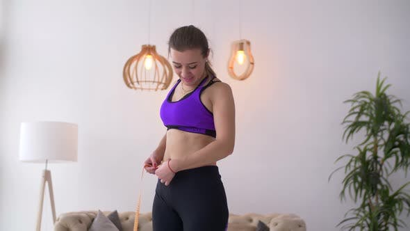 Cover Image for Happy Woman Measuring Her Waist with Tape Measure