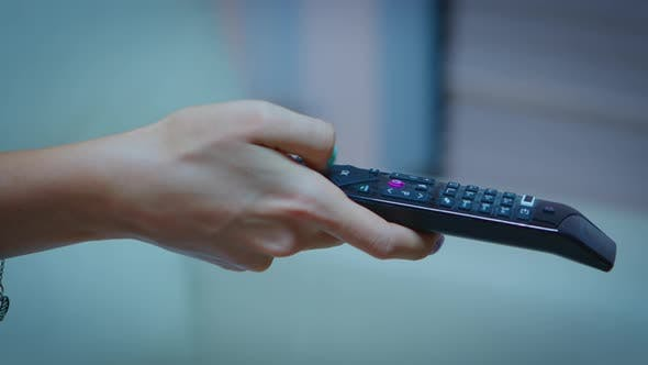 Television Remote Control in Woman Hands Pointing To Tv
