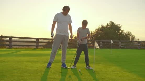 Thumbnail for Man with His Son Playing Golfers on Perfect Golf Course at Summer Day