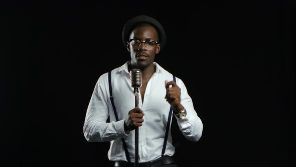 Thumbnail for African American in a Studio Is Singing Songs Into a Microphone. Black Background