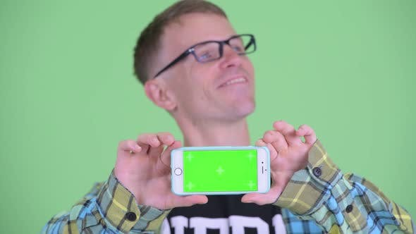 Cover Image for Face of Happy Nerd Man Thinking While Showing Phone
