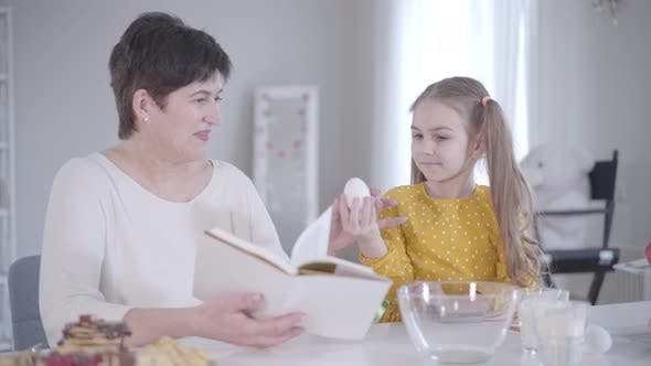Thumbnail for Cute Caucasian Little Girl Gathering Ingredients for Pancakes As Grandmother Reading the Recipe