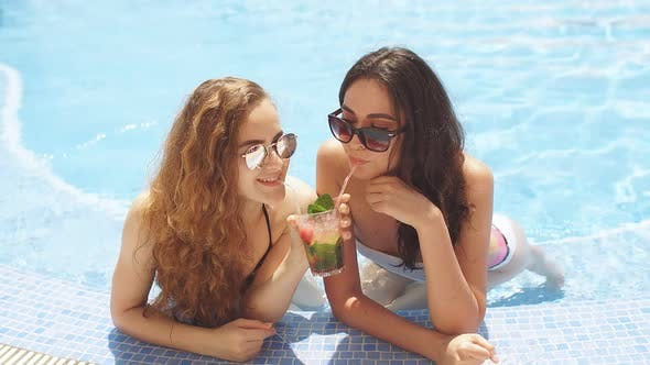 Two Young Girlfriends Sitting in Cool Swimming Pool in Resort Hotel on Vacation