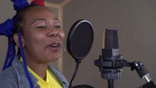 Young Black Woman Musician Singing Into a Microphone in a Recording Studio