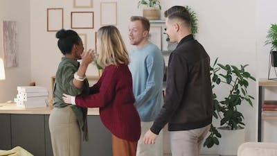 Young Woman Greeting Friends at Home