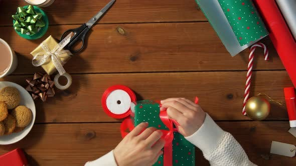 Thumbnail for Hands Packing Christmas Gift and Tying Bow