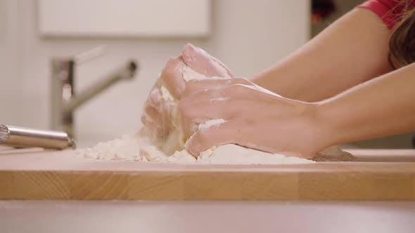 Thumbnail for A Woman Kneads Crumbly Pastry Dough on a Kitchen Counter - Closeup - Slow Motion