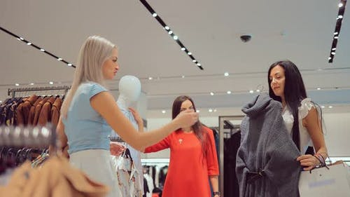 Girl Chooses Clothes in the Store with Her Friends and Goes to the Cashier