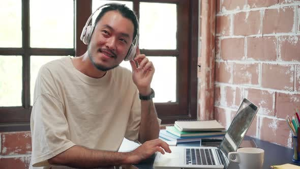 Asia guy headphones listening music and working on laptop in living room at house