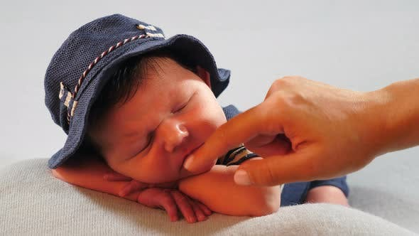 Tiny Adorable Newborn Baby Boy Lying Asleep Dressed in Hat and Knitted Costume with Stripped Sleeves