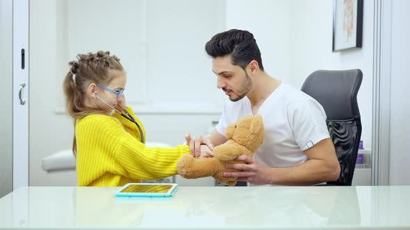 Side View of Smiling Male Pediatrician Talking with Cute Girl Listening Teddy Bear with Stethoscope