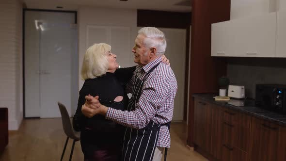 Senior Couple in Love Have Romantic Evening, Dancing Together in Kitchen, Celebrating Anniversary