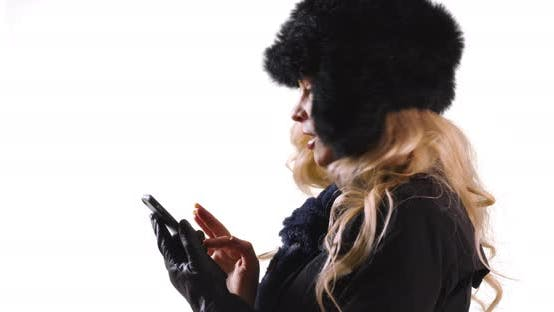 Thumbnail for Profile of woman in fur cap and scarf texting on phone in studio with copyspace