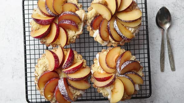 Thumbnail for Homemade Crumble Tarts with Fresh Plum Slices Placed on Iron Baking Grill