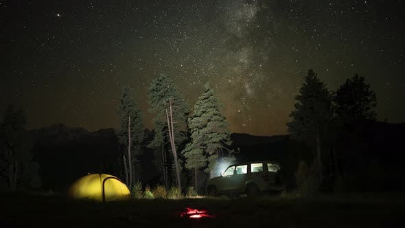 Time Lapse of Camping with a Car, Tent and Campfire at Night